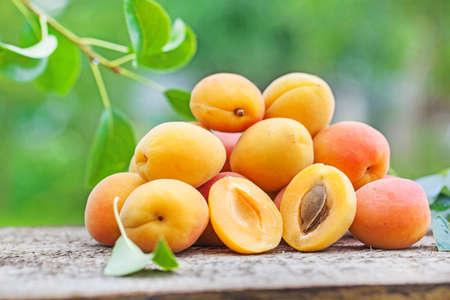 Aprikose auf Holz, grüner Naturhintergrund