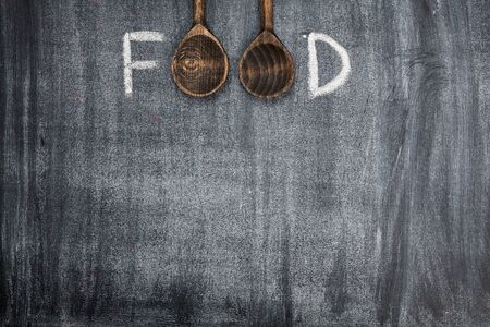 Food title written with chalk on blackboard with two wooden spoon