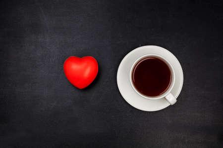 Tasse Tee auf schwarzer Oberfläche. Ansicht von oben. Standard-Bild