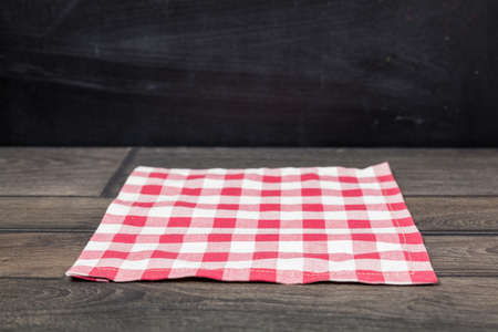 Red napkin on dark wooden table. Copy space. Black wall background. Front view.