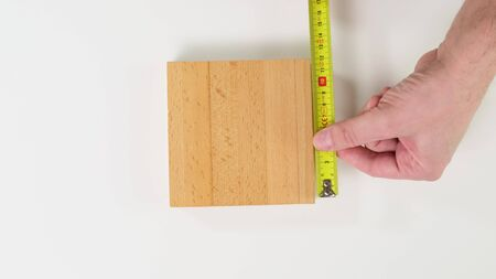 Measuring wood object with tape on white background. 版權商用圖片 - 143800200