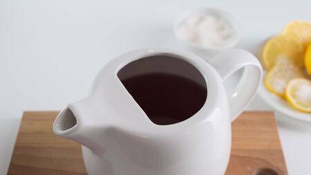 Versé de l'eau bouillante dans une théière blanche sur la table.