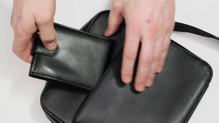 Put a leather wallet in a man handbag.