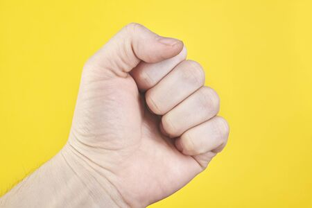 Hand with clenched a fist, isolated on a yellow background. Close up