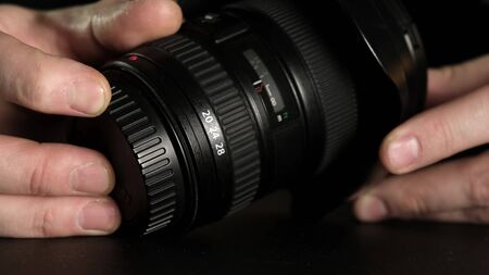 A mans hand turns the focus wheel on the lens. Close up.