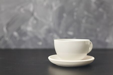 A white cup on the black table. On gray background Zdjęcie Seryjne