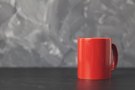 Red cup gray background ron black table. Copy space