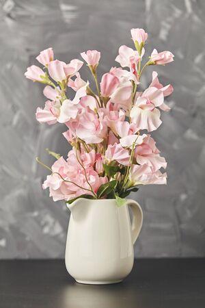 Pink flower in vase on black table on gray background. Close up Standard-Bild
