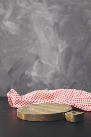 Red napkin at empty cutting board on gray background.