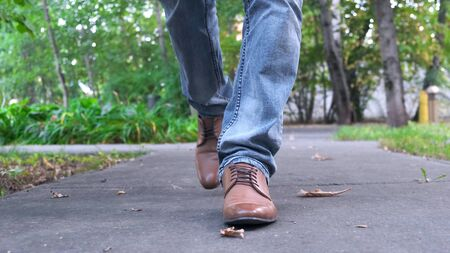 View of man's walking legs in blue jeans, black leather shoes. Close up.
