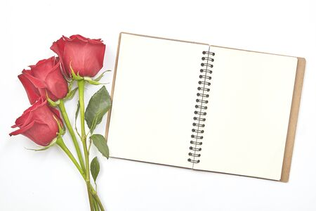 Top view shot of empty blank notebook diary and red roses on white table