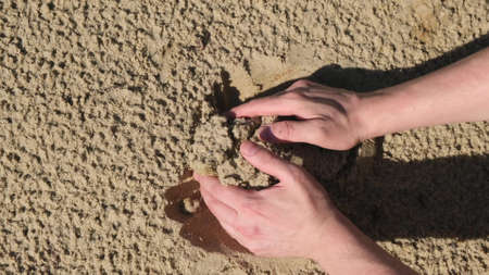 Adult Male Hand Takes Sand Close up