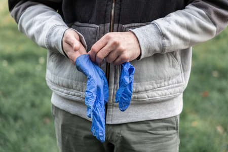 Hand in latex glove on blurred nature background outdoors