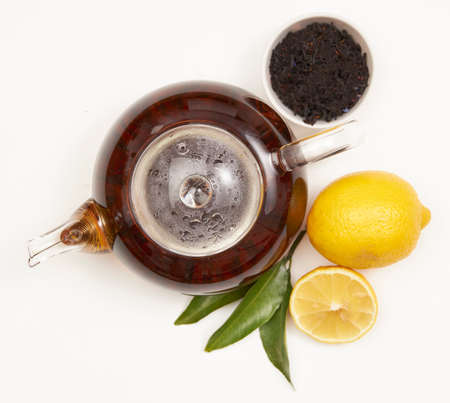 Teapot and cup of tea with green leaves and lemon on white
