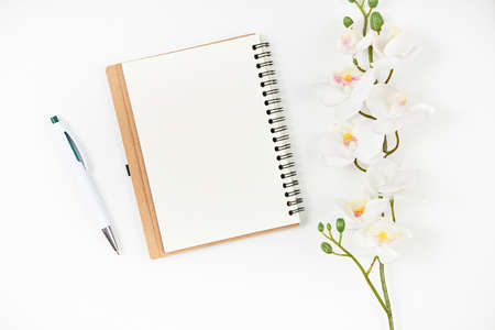 Blank notepad, pen and flower on wooden table. View from above