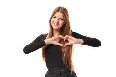 Portrait of young girl showing heart with her hands. White background. Studio shot.