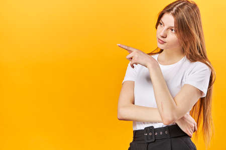 Portrait of a young woman pointing fingers away at copy space isolated over yellow background