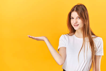 Young girl, showing holding copy space on palm. Isolated over bright vivid yellow background
