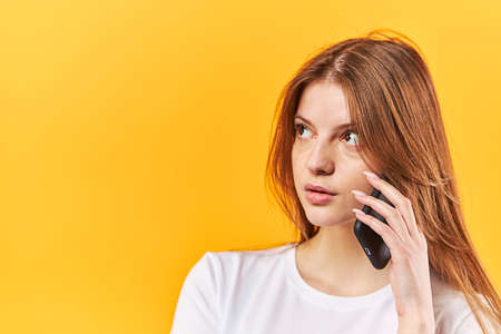 Portrait woman talking on mobile phone and looking away isolated over yellow background