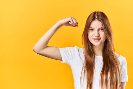 Young Woman Shows Muscles On Arm, Shows Biceps. The Concept Of Strong, Powerful People