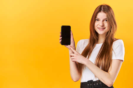 Portrait girl holding in hands cell showing black screen isolated on bright vivid shine yellow background