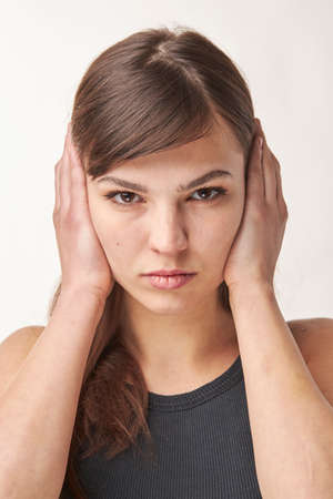 Portrait of a nice looking woman covers her ears Close up Stock Photo