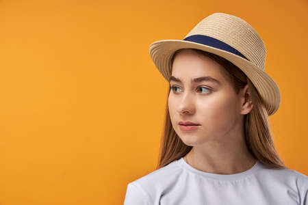 Portrait of joyful teenage girl showing, orange background with copy space Stock Photo