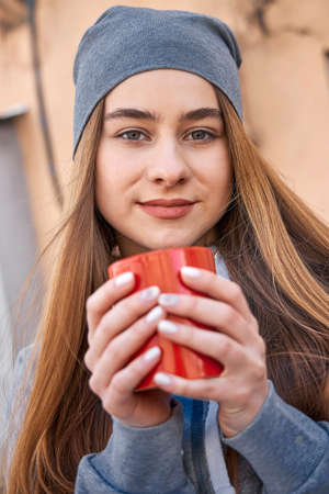 Portrait of smiling beautiful with cup of coffee, relaxing outdoor Stock Photo