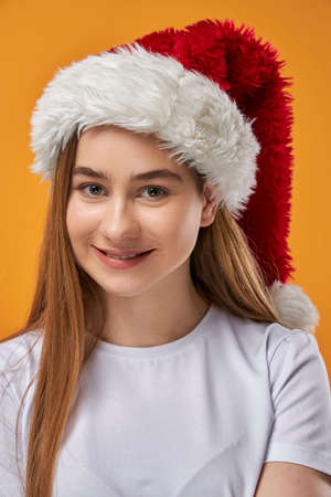 Happy girl in Santa hat holding looking at camera and smiling, orange studio background Stock Photo