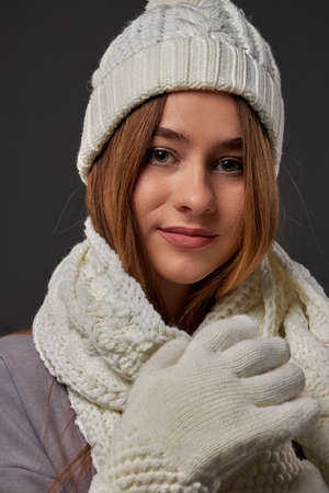Smiling girl portrait wearing white hat, scarf, gloves closeup