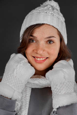 Cute woman wrapped up warm in winter white clothes