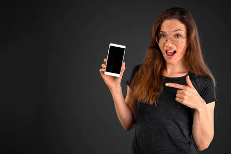 Closeup of young attractive girl smiling isolated on grey background holding and showing blank smartphone with copyspace Stock Photo