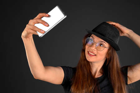 Beautiful young woman taking selfie on smartphone.