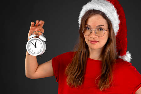 Young girl santa claus hat holding an white alarm clock