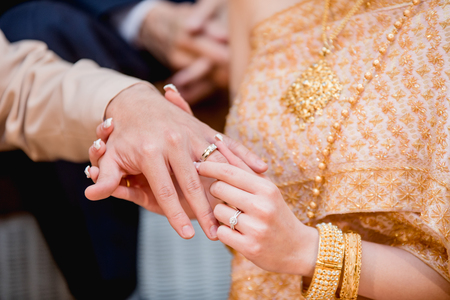 hands of a wedding couple, Groom put a ring on finger of his lovely wife, wedding ceremony