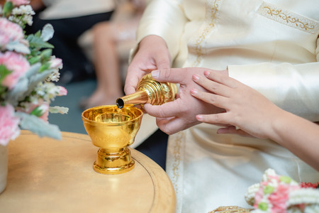 close up of a hand wedding couple pour water of dedication, Thailand wedding