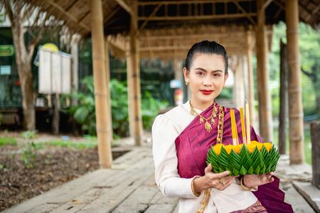 Beautiful woman ware Traditional Thai dresses hold floating basket or kratong, loy kratong festival in Thailand Фото со стока