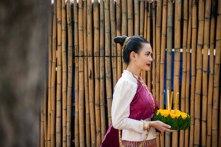 Beautiful woman ware Traditional Thai dresses hold floating basket or kratong, loy kratong festival in Thailand 스톡 콘텐츠 - 133214305