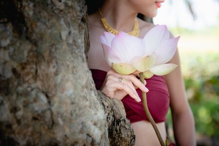 Asian woman collecting lotus flowers and she wear Traditional Thai dresses, Thailand 스톡 콘텐츠 - 133214306
