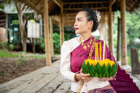 Beautiful woman ware Traditional Thai dresses hold floating basket or kratong, loy kratong festival in Thailand 스톡 콘텐츠 - 133214307