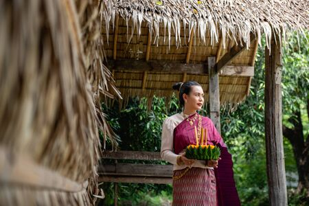 Beautiful woman ware Traditional Thai dresses hold floating basket or kratong, loy kratong festival in Thailand 스톡 콘텐츠 - 133214314
