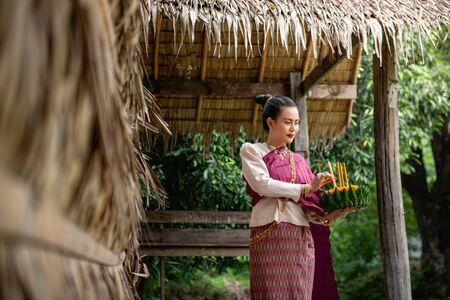 Beautiful woman ware Traditional Thai dresses hold floating basket or kratong, loy kratong festival in Thailand 스톡 콘텐츠 - 133214317
