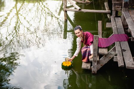 Beautiful woman ware Traditional Thai dresses hold floating basket or kratong, loy kratong festival in Thailand 스톡 콘텐츠 - 133214324
