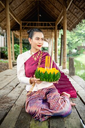 Beautiful woman ware Traditional Thai dresses hold floating basket or kratong, loy kratong festival in Thailand 스톡 콘텐츠 - 133214326