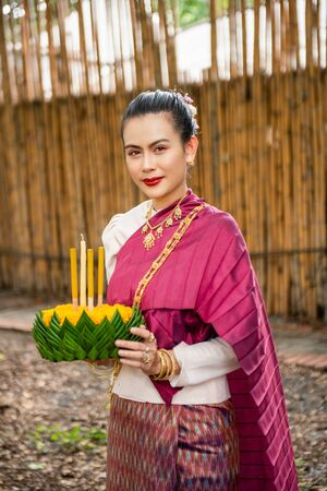 Beautiful woman ware Traditional Thai dresses hold floating basket or kratong, loy kratong festival in Thailand 스톡 콘텐츠 - 133214330
