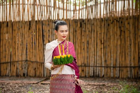 Beautiful woman ware Traditional Thai dresses hold floating basket or kratong, loy kratong festival in Thailand 스톡 콘텐츠 - 133214299