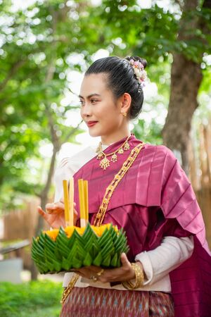 Beautiful woman ware Traditional Thai dresses hold floating basket or kratong, loy kratong festival in Thailand 스톡 콘텐츠 - 133214178
