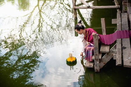 Beautiful woman ware Traditional Thai dresses hold floating basket or kratong, loy kratong festival in Thailand 스톡 콘텐츠 - 133214186