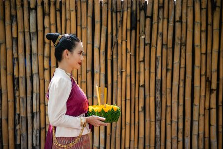 Beautiful woman ware Traditional Thai dresses hold floating basket or kratong, loy kratong festival in Thailand 스톡 콘텐츠 - 133214191