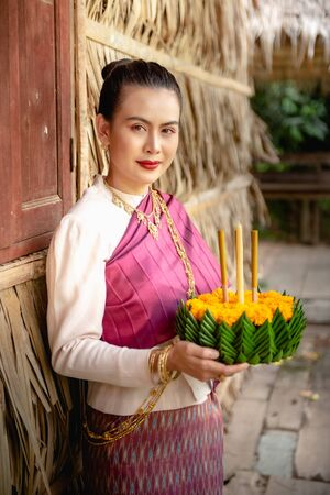 Beautiful woman ware Traditional Thai dresses hold floating basket or kratong, loy kratong festival in Thailand 스톡 콘텐츠 - 133214193